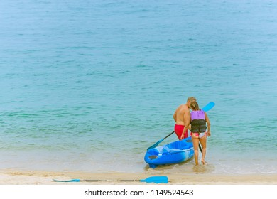 The lovers are dragging their kayak to paddle space sea in background