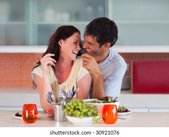 Lovers eating fruit in the kitchen