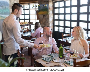 Lovers eating healthy vegetarian food in a restaurant while handsome waiter is serving them