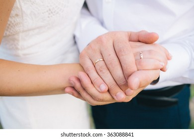 lovers holding hands with gold wedding rings, the bride and groom
