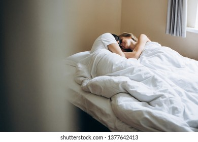Lovers hug in the morning in a white bed