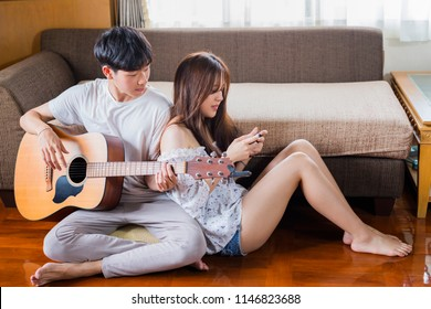 Lovers in a living room. Young asian man playing guitar while asian woman doing online shopping on mobilephone in the living room at home and leave space for adding your content.