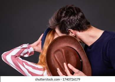 Lovers man and woman hide their kiss behind a cowboy hat