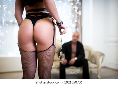Lovers man and woman are preparing for role playing games. Dominate obey undress seduce a partner. Girl dressed in stockings on suspenders, wearing sexy underwear. new sensual date idea. Thematic bdsm