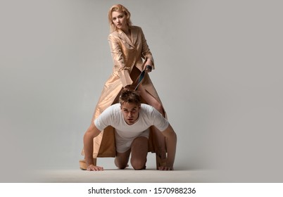 Lovers man and woman are preparing for role playing games. Dominatrix blonde woman holding her husband in collar and make him obey. New sensual date idea concept