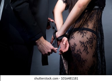 Lovers man and woman are preparing for role-playing games. Dominate obey undress seduce a partner. Girl dressed in black lacy negligee, wearing sexy underwear. A sensual date idea. Thematic bdsm party