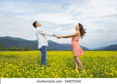 Lovers man and woman walk on the flower field. A romantic date.