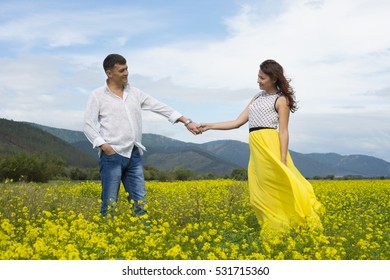 Lovers man and woman walking in a flower field holding hands.