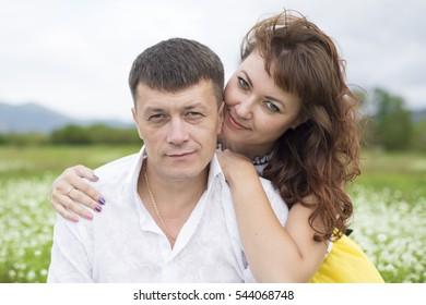 Lovers men and women on a beautiful flower field. A romantic date.