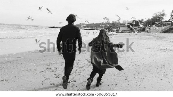 lovers on the beach, love story by the sea, free running lovers. Film noise, black & white