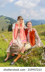 Lovers pants in fashionable traditional Bavarian Dirndl and leather with hat sitting on a rock and enjoy the scenery / Lovers pants in fashionable traditional Bavarian Dirndl and leather with hat