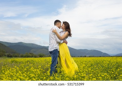 The lovers passionately embrace each other on the flowery meadow.