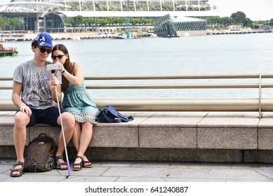 Lovers people are watching image on phone at waterfront near Merlion Singapore on April 23, 2017.