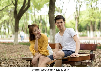 Lovers play guitar outdoors