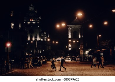 lovers running through empty road in the evening city street. stylish couple in love having fun and holding hands in city lights. modern woman and man romantic french atmospheric moment