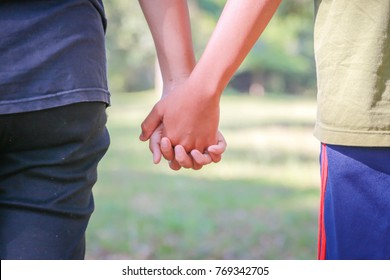 Lovers shake hands in the garden, blurred background
