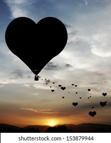 Lovers sowing hearts from a heart shape hot air balloon floating in a surreal sunset sky.