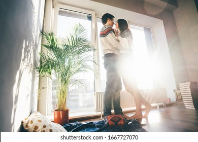 Lovers standing near the window, looking to each other and kissing. Magic light.