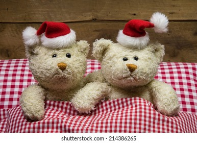 Lovers: two teddy bears sitting on christmas with hats in the bed.