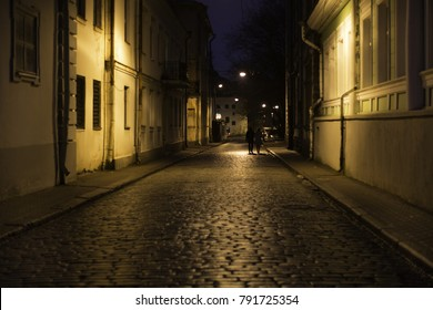 Lovers walk along the night street in the light of street lamps. black walls and yellow light on an empty street lined with ancient paving stones.