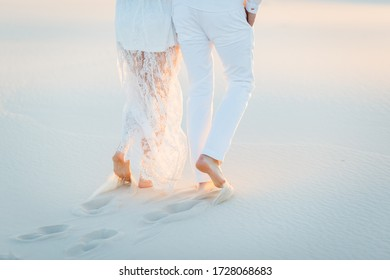 Lovers walk barefoot on the sand in the white desert. Love in the desert newlyweds.