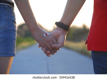 "Lovers walk and holding hands on the road in evening. They have the necklace in heart shape is mean ""I love You"" in concept about lovers"