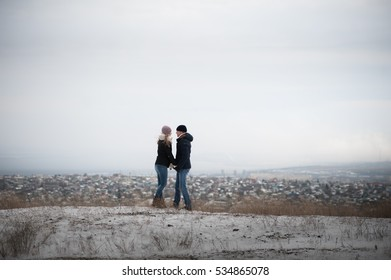 Lovers walk in the winter on the mountain on the background of the city. Couple in love running around in the snow forest. Winter Love Story. walking and running around in the winter.