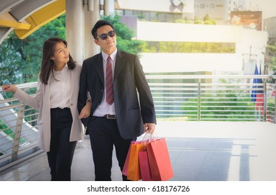Lovers, women and men carrying many paper bags, happily shopping on weekends.