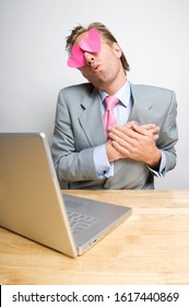 Lovestruck businessman sitting swooning at his desk with hearts in his eyes looking at the laptop computer on his desk