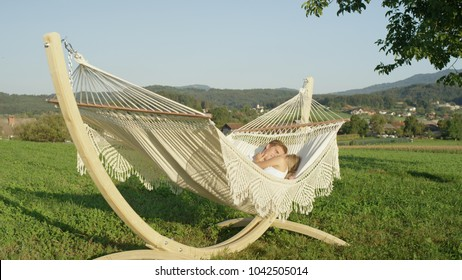 Lovestruck couple talks and cuddles on fabric sling during lovely date outdoors. Attractive blonde girl caresses handsome man's face as they lounge in romantic wooden hammock in tranquil green nature.