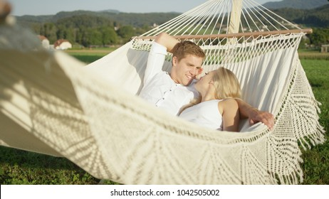 Lovestruck young girlfriend and boyfriend in love talking in hammock in nature. Lovely couple talking as they relax on sling in sunny spring countryside. Happy boy and girl lounging on romantic swing.