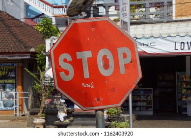 Lovina, Bali, Indonesia - August 8, 2018: Red stop sign with white letters in the city of Lovina, Indonesia.