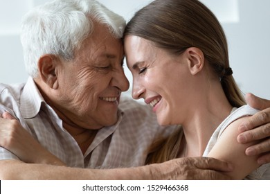 Loving 70s grandfather touch foreheads of adult granddaughter relative people hugging at home close up side view faces, hoary elderly father cuddle grown up daughter showing love and devotion concept