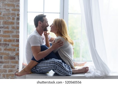 Loving adult couple hugging in bedroom