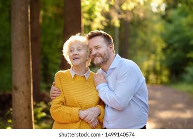 Der liebende erwachsene Sohn liebt seine fröhliche ältere Mutter während des Spazierens im Sommerpark. Zwei Generationen Familie.