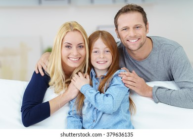 Loving affectionate happy young family with a pretty little redhead daughter posing arm in arm on a comfortable sofa at home smiling at the camera
