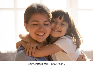 Loving affectionate little kid daughter hugging happy mom cuddling enjoying moment of love tenderness, cute small child girl embracing mother holding tight showing sincere care, warm relationships