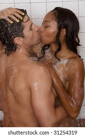 Loving affectionate nude heterosexual couple in shower engaging in sexual games, hugging and kissing. Mid adult Caucasian men in late 30s and young black African-American woman in 20s