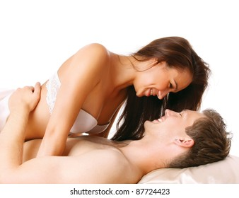 Loving affectionate nude heterosexual couple on bed isolated on white background