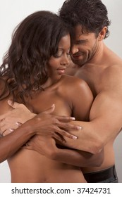 Loving affectionate nude interracial heterosexual couple in affectionate sensual hug.