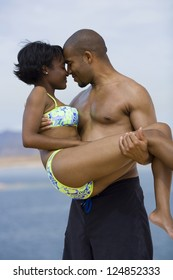 Loving African American couple embracing on the beach