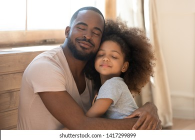 Loving african american family cute funny child daughter embrace black father feel love affection together, happy dad and little kid girl hug cuddling bonding with eyes closed at home on fathers day