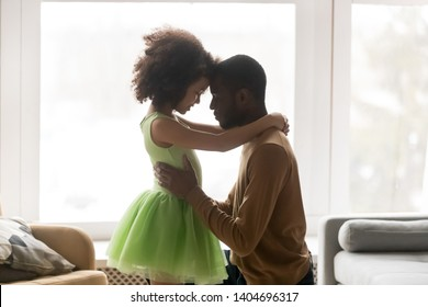 Loving African American father and preschool daughter touching foreheads, enjoying tender moment together, daddy and little girl in princess dress standing in living room at home, close up
