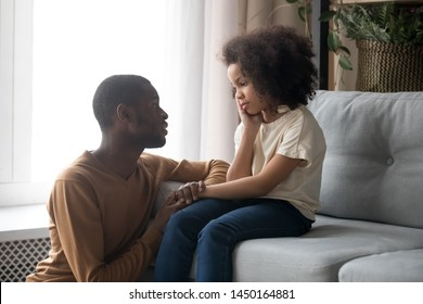 Loving african American father talk with upset preschooler daughter helping with problem, caring black young dad speak with sad girl child holding caressing hand, show support and understanding