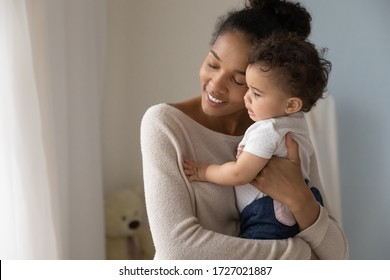 Loving african American mother hold in arms embrace little baby girl child enjoy tender family moment at home, caring young biracial mom hug cuddle cute toddler infant, childcare, maternity concept