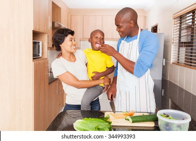 loving african father feeding son a piece of tomato in kitchen