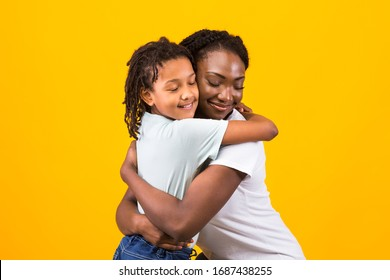 Loving African Woman Embracing Her Child, Looking Happy And Calm. Yellow studio wall, copy space