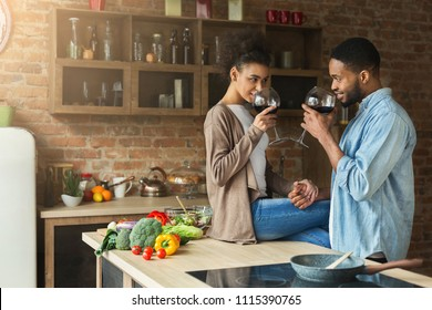Loving african-american couple drinking wine in kitchen. Family preparing dinner