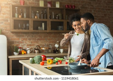 Loving african-american couple preparing vegetable salad for dinner in loft kitchen