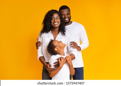 Loving afro family with daughter embracing and smiling at camera over yellow background, free space